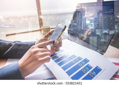 Double exposure of businessman using smart phone at office with city night background