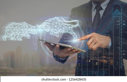 Double exposure of businessman using the tablet with virtual reality technology showing polygonal bull and bear shape for trading information over cityscape and financial graph background