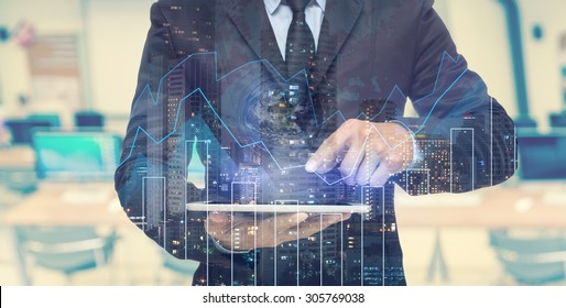 Double exposure of businessman using the tablet with cityscape and financial graph which have earth and world map on computer blurred background, Elements of this image furnished by NASA