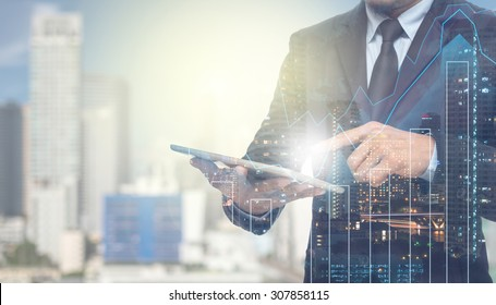 Double exposure of businessman using the tablet with cityscape and financial graph on blurred building background, Business Trading concept