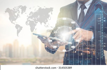Double exposure of businessman using the tablet with cityscape and financial graph on blurred building with world map and mail background, Elements of this image furnished by NASA