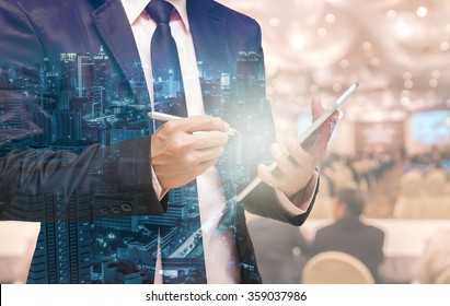 Double exposure of Businessman using the tablet on the Abstract blurred photo of conference hall or seminar room with attendee background