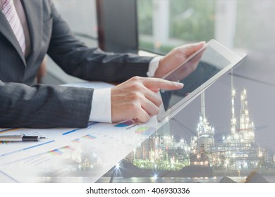 Double exposure businessman using the tablet in office with refinery and financial graph on blurred oil refinery background, Business Trend concept.