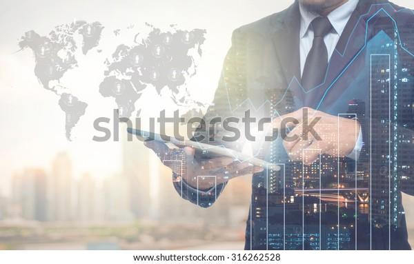 Doppelte Exposition von Geschäftsleuten, die die Tablette mit Stadtbild und Finanzdiagramm auf unscharfem Gebäude mit Weltkarte und Logo-Hintergrund verwenden, Elemente dieses von der NASA bereitgestellten Bildes