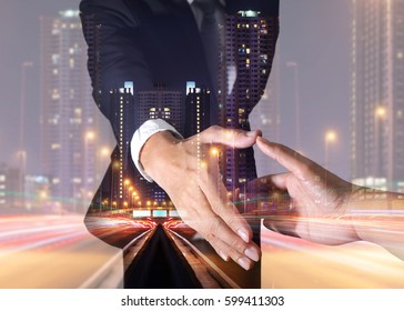 Double exposure of businessman will handshaking for business relationship, light trails on the street and urban in the night as business, commitment and partnership concept.