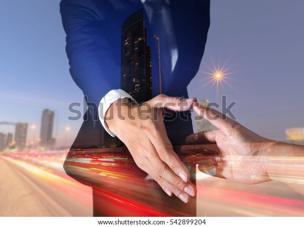 Double exposure of businessman will handshaking for business relationship, light trails on the street and urban at dusk, night as commitment and partnership concept.