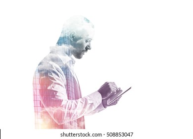 Double exposure of a businessman working on a tablet pc with glass facade and sky side view isolated on white