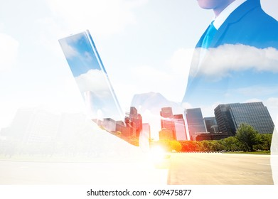 double exposure of businessman working on his laptop with city background