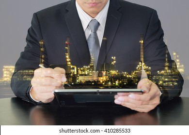 Double exposure of businessman working with tablet and oil refinery industry plant in the night as Energy and Technology concept.