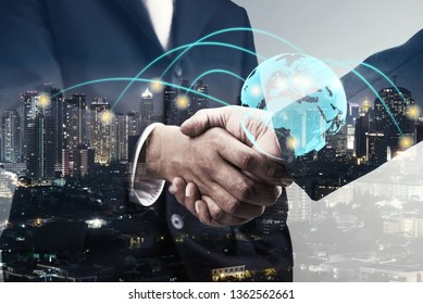 double exposure of businessmen handshake and global simulation connecting technology with blur city night and network connection, successful and partnership concept