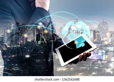 double exposure of businessmen using tablet show global simulation connecting technology with blur city night and network connection concept