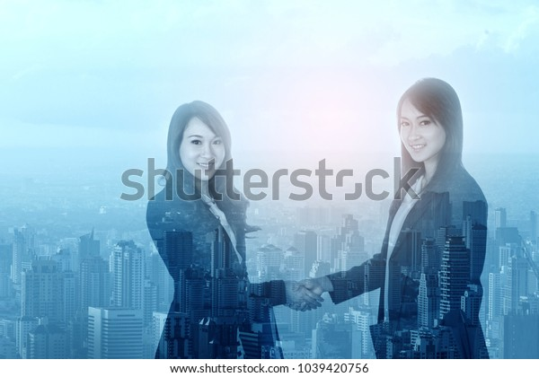 Double exposure of businesswoman handshaking and american business people after a successful business deal on city background in Thailand.