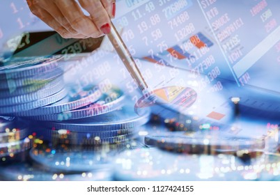 Double exposure businesswoman holding pen on summery graph with coin and bokeh background. Businesse concept.