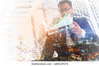 Double exposure city background.Close up of businessman presenting digital charts.Business growth, progress or success concept. Businessman is showing a growing virtual hologram stock.