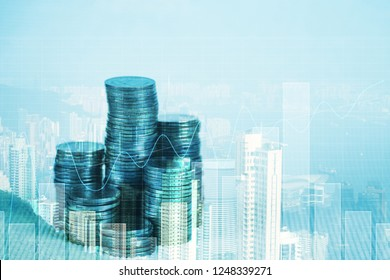 Double exposure of coin stack with financial graph over city and office building background, business and financial concept idea.