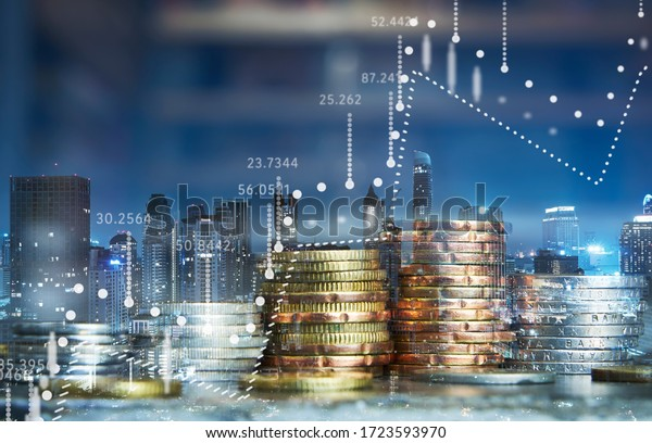 Double exposure of coins stack with graph chart and night cityscape. Economic, business, financial and stock market growth concept.