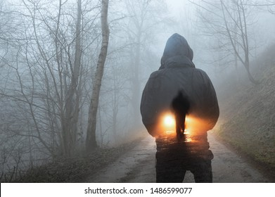 A double exposure concept. A hooded figure looking at a silhouette of a man in front of car headlights. On a spooky forest track on a misty winters evening.