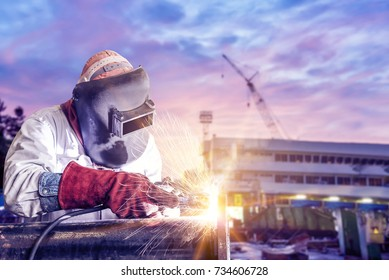 double exposure concept, worker steel with by arc welder piping welding building in shipyard background soft monotone