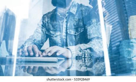 Double exposure concept.Bearded man working in the office.Coworker typing at a computer keyboard.Woman holding smartphone hand.Skyscraper office building on blurred background.Horizontal