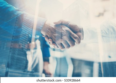 Double exposure concept.Close up view of business partnership handshake concept.Photo two businessman handshaking process.Skyscraper office building on the blurred background.Horizontal,flares effect