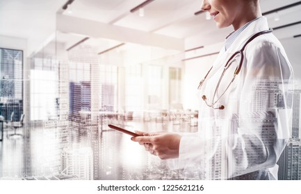 Double exposure of confident female doctor in white sterile coat standing inside hospital office and modern cityscape view on background. Concept of modern technologies for medical industry