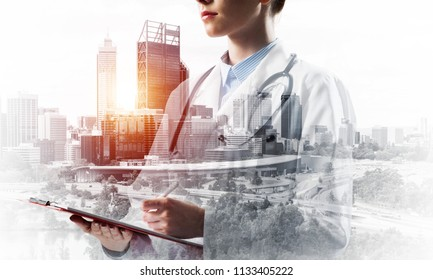 Double exposure of confident woman doctor standing with pen and notebook in hands and modern cityscape view on background. Medical industy concept