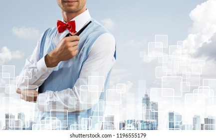 Double exposure of confident and young businessman in smart-casual wear smoking pipe and modern cityscape with business and media interface. Concept of new technologies for modern business.