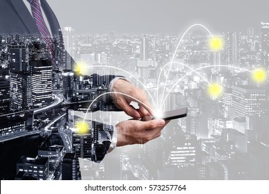 Double exposure of connectivity concept - businessman using smartphone with connected line with city overlay