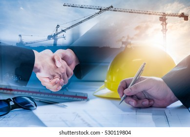 Double exposure of construction site and Business people shaking hands after the contract is signed for construction management Infrastructure plan guidelines concept.