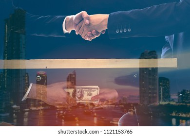 Double exposure of corruption concept two businessman sealing the deal with a handshake and receiving a bribe money on modern city black background. Hands passing money under table corruption bribery.