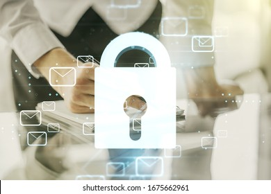 Double exposure of creative lock hologram with email symbols and man hand writing in notebook on background. Information security concept