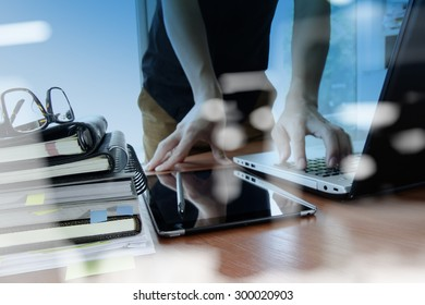 double exposure of designer hand working with digital tablet and laptop and notebook stack and eye glass on wooden desk in office