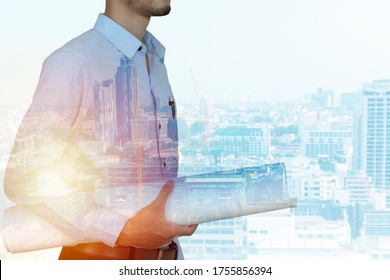 Double exposure of engineer holding blueprint with city background.
