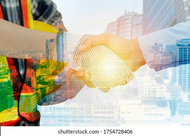 Double exposure of engineer and investor shaking hands with city background.