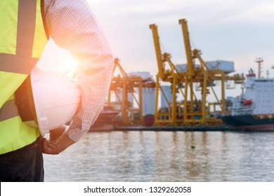 Double exposure of  Engineer or Safety officer holding hard hat with Logistic Import Export background .