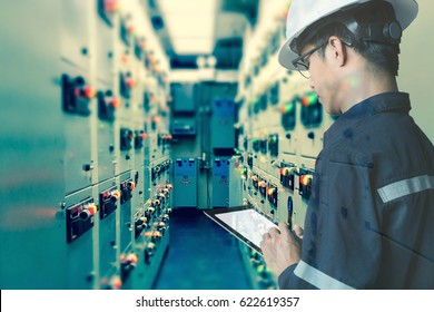 Double exposure of  Engineer or Technician man working with tablet in switch gear electrical room of oil and gas platform or plant industrial for monitor process, business and industry concept