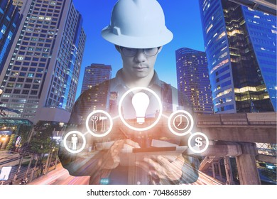 Double exposure of Engineer or Technician man with business industrial tool icons while using tablet with light of night commercial building for constrution business concept.
