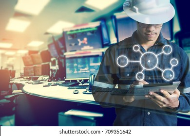 Double exposure of Engineer or Technician man with business industrial tool icons while using tablet with monitor of computers room  for oil and gas industrial 4.0 business concept.