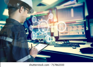 Double exposure of Engineer or Technician man with business industrial tool icons while using tablet with monitor of computers room  for oil and gas industry 4.0 business concept.