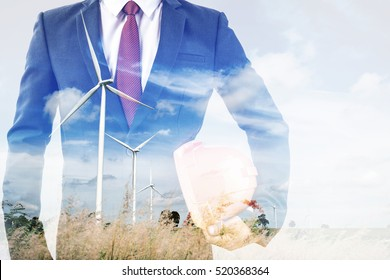 double exposure of engineer or worker hold in hand yellow helmet for workers security with wind turbine green energy plant background