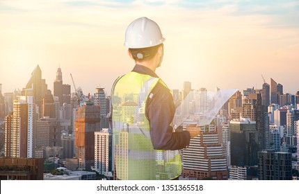 Double exposure of Engineers wearing a helmet holding a blueprint with city background and high building.