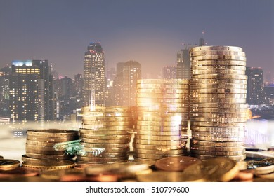 double exposure of golden Coin stacks on table with blur city night background, business investment concept