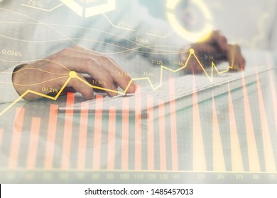 Double exposure of graph with man typing on computer in office on background. Concept of hard work. Closeup.