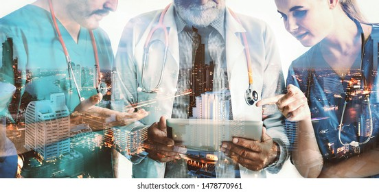 Double exposure group of happy doctor surgeon and nurse with tablet in meeting on city night background, Healthcare and medical concept