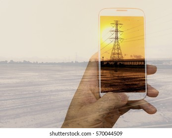 Double exposure with hand hilding smartphone and high voltage pylon tower.Concept for telecommunication technology with sunset background.