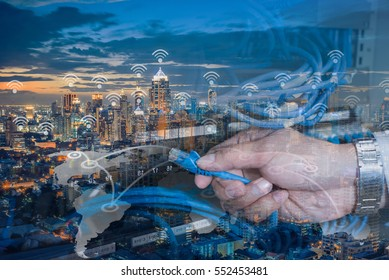 Double Exposure Hand holding lan cable and city wifi connection concept
