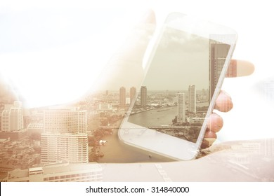 Double exposure of hand with mobile phone and bangkok cityscape in the background