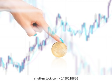 Double exposure of hand pointing to bitcoin and chart.
