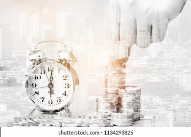 Double exposure of Hand putting money coins to stack of coins and retro alarm clock on city background for Real estate investments and business concept