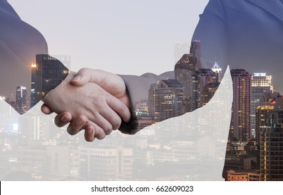 Double Exposure of of handshake and city on background blurred downtown urban. Internet of thing technology concept.